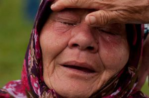 A Bosniak woman Senija Rizvanovic cries near the graves of her two sons, in Srebrenica, Bosnia. Photo by Amel Emric/AP
